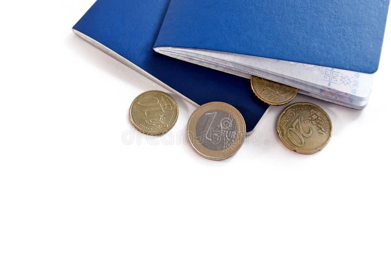 Dos pasaportes azules y monedas euro del dinero fotografía de archivo libre de regalías