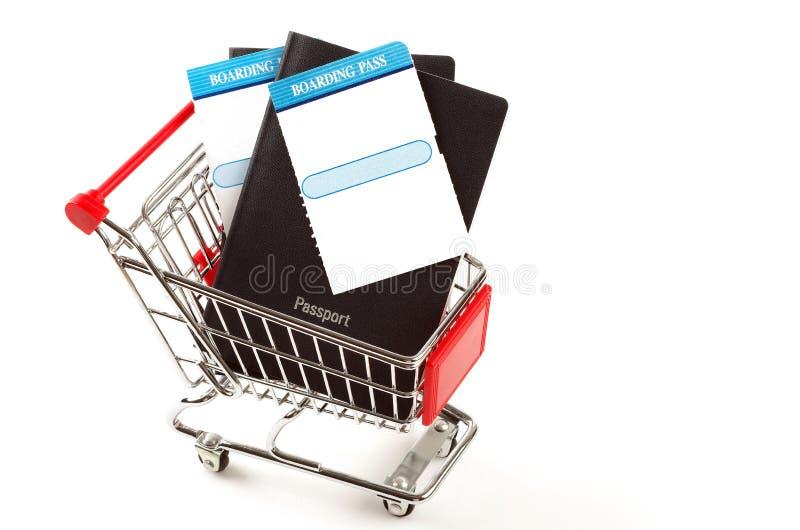 Dos pasaportes y tarjetas de embarque dentro de un carro de la compra imagen de archivo