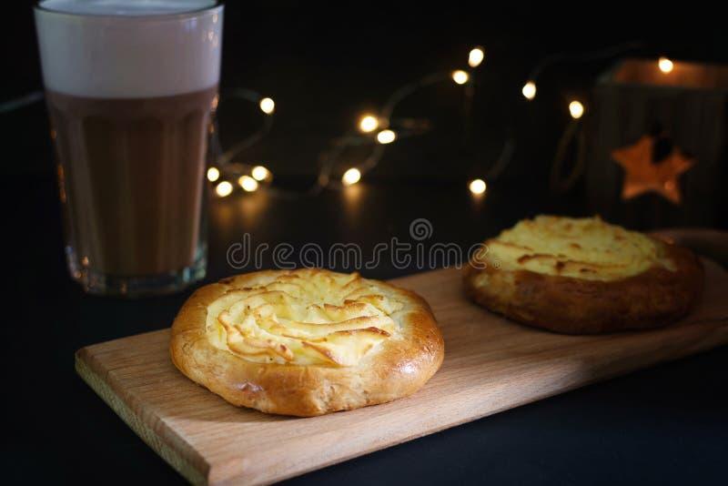 Dos pasteles de queso con mentira del requesón en un tablero de madera En las luces del fondo de la guirnalda en la falta de defi imagenes de archivo