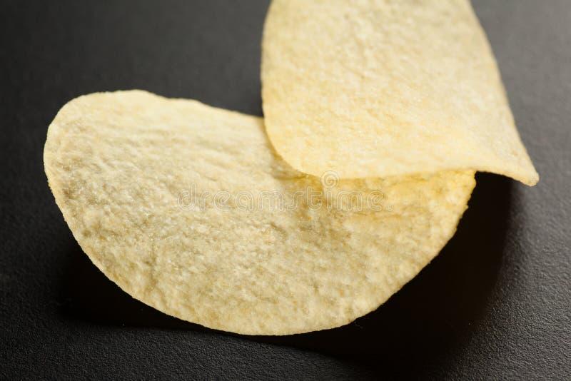 Dos patatas fritas de oro en el negro, foco selectivo, primer fotografía de archivo