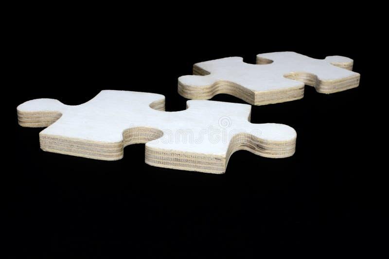 Dos pedazos de madera del rompecabezas en un fondo negro fotos de archivo