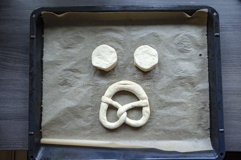 Dos pedazos de pasta cruda y de un pretzel se presentan en una bandeja bajo la forma de cara triste, contra una tabla de madera t fotografía de archivo libre de regalías