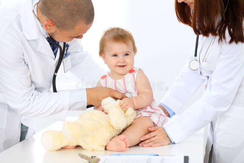 Dos pediatras están tomando el cuidado del bebé en hospital La niña está examinando por el doctor con el estetoscopio salud fotografía de archivo libre de regalías