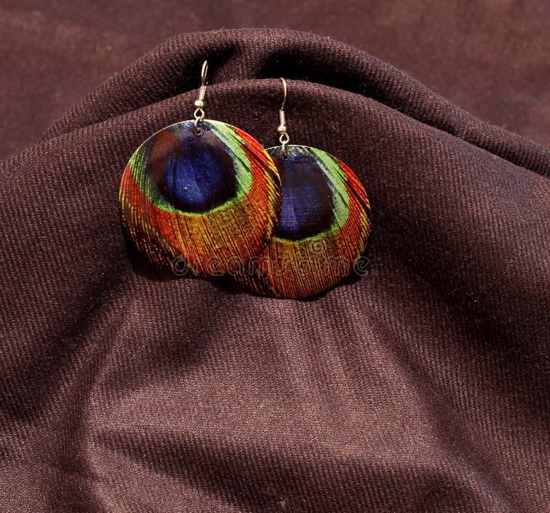 Dos pendientes con diseño de la pluma del pavo real del multicolor fotografía de archivo libre de regalías