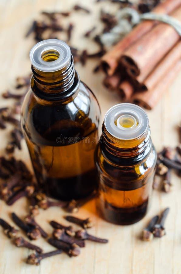 Dos pequeñas botellas de aceite esencial del canela y de clavo fotos de archivo