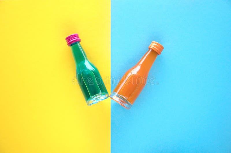 Dos pequeñas botellas de cristal con un cóctel azul y anaranjado en un fondo azul y amarillo Dos pequeñas botellas multicoloras c imagenes de archivo