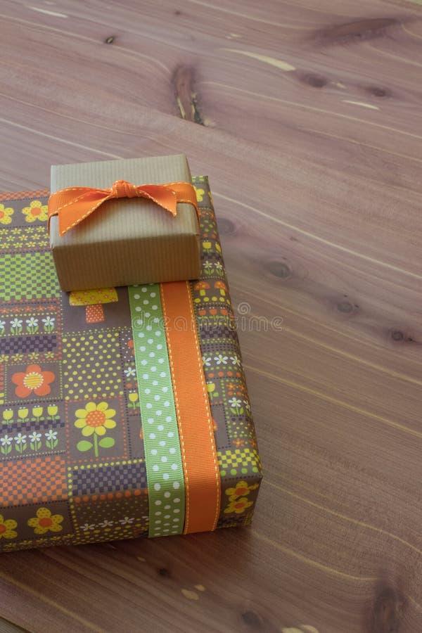 Dos pequeñas cajas de regalo en anaranjado y marrón verdes con las cintas, estilo retro, fondo de madera neutral fotos de archivo