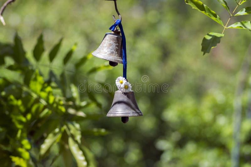 Dos pequeñas campanas orientales metálicas que cuelgan en el jardín, día soleado, verdor imagen de archivo libre de regalías