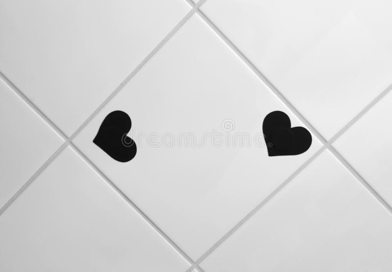 Dos pequeñas etiquetas engomadas en forma de corazón negras en la teja esmaltada imagenes de archivo