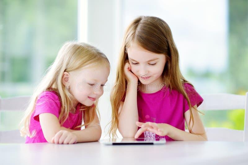 Dos pequeñas hermanas adorables que juegan con una tableta digital en casa Niño en una escuela primaria imagen de archivo libre de regalías