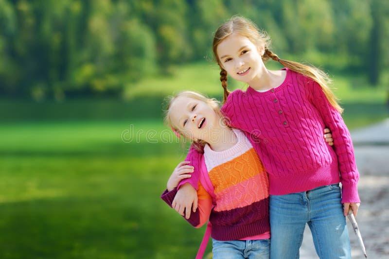 Dos pequeñas hermanas adorables que ríen y que abrazan en día de verano caliente y soleado cerca del lago Konigssee, Alemania foto de archivo libre de regalías