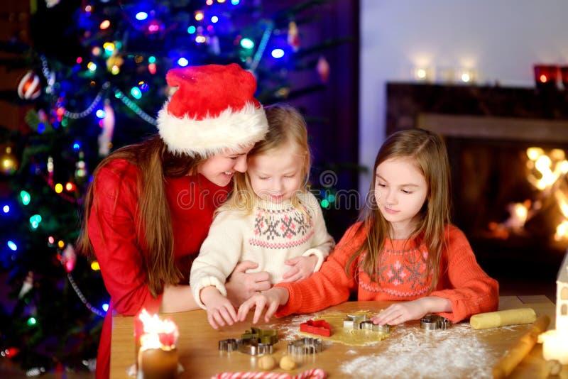 Dos pequeñas hermanas adorables y sus galletas de la Navidad de la hornada de la madre por una chimenea imagenes de archivo
