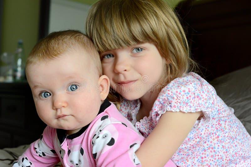 Dos pequeñas hermanas caucásicas adorables se sientan juntas La pequeña hermana abraza a su bebé-hermana imagenes de archivo