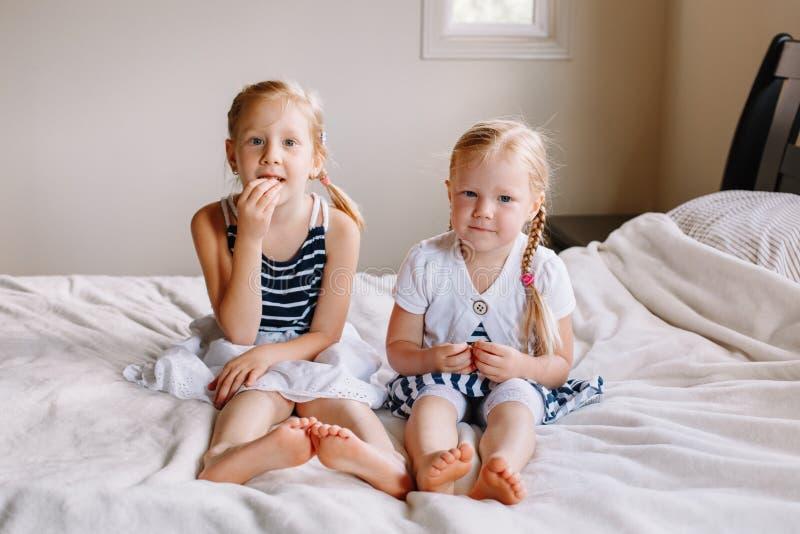 Dos pequeñas hermanas caucásicas rubias pelirrojas adorables lindas de las muchachas que se sientan junto en cama en casa foto de archivo