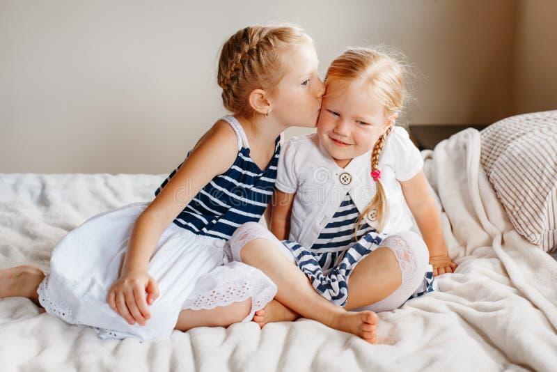 Dos pequeñas hermanas caucásicas rubias pelirrojas adorables lindas de las muchachas que se sientan junto en cama en casa fotos de archivo libres de regalías