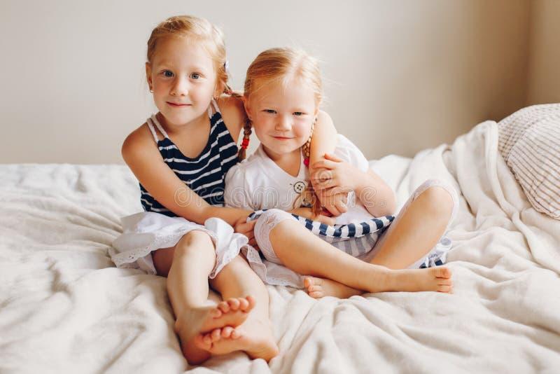 Dos pequeñas hermanas caucásicas rubias pelirrojas adorables lindas de las muchachas que se sientan junto en cama en casa fotos de archivo