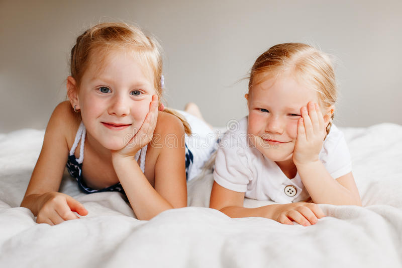 Dos pequeñas hermanas caucásicas rubias pelirrojas adorables lindas de las muchachas que se sientan junto en cama en casa imagen de archivo