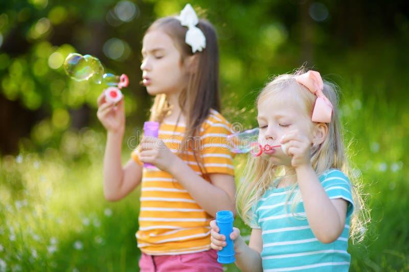 Dos pequeñas hermanas divertidas que soplan burbujas de jabón al aire libre fotografía de archivo