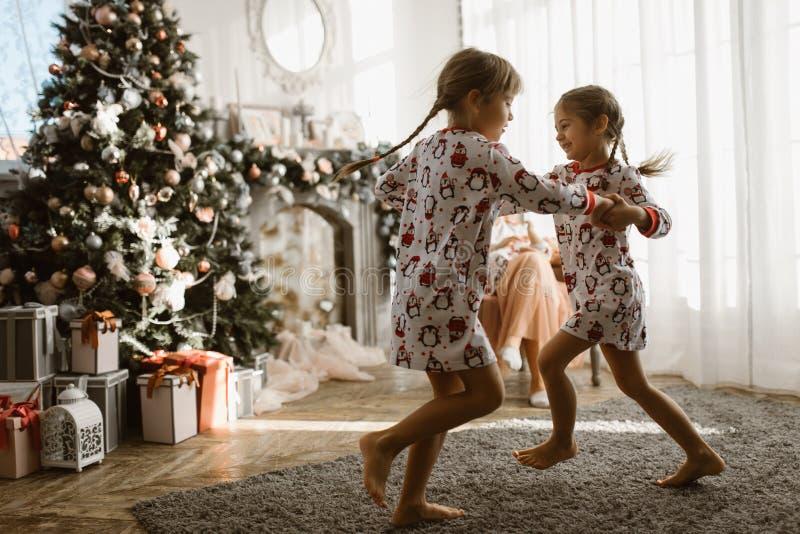 Dos pequeñas hermanas en los pijamas que tienen árbol del Año Nuevo de la diversión con soldado enrollado en el ejército imagen de archivo libre de regalías