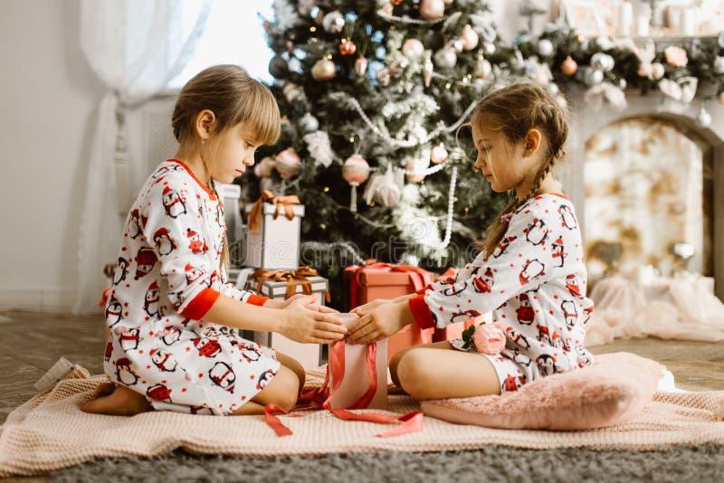 Dos pequeñas hermanas en pijamas se sientan en la alfombra y abren los regalos del Año Nuevo en el cuarto acogedor ligero con A foto de archivo libre de regalías