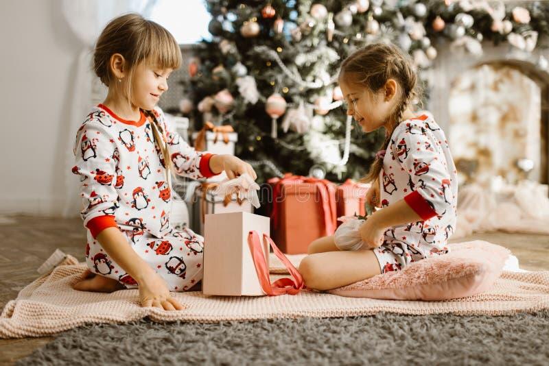 Dos pequeñas hermanas en pijamas se sientan en la alfombra y abren los regalos del Año Nuevo en el cuarto acogedor ligero con A fotografía de archivo libre de regalías