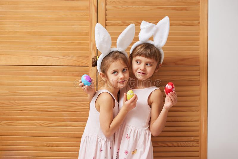 Dos pequeñas hermanas encantadoras divertidas en los vestidos con los oídos de conejo blancos en sus cabezas sostienen los huevos imagen de archivo libre de regalías