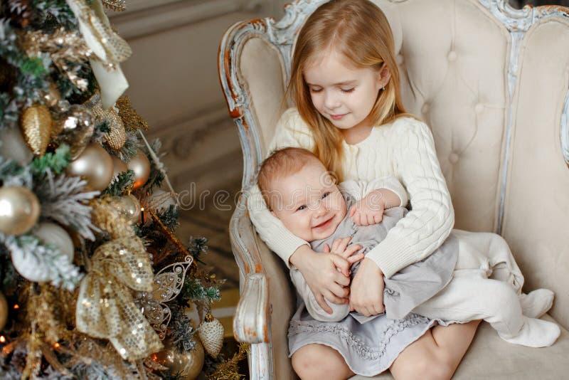 Dos pequeñas hermanas encantadoras que se sientan en una silla y que sonríen en th fotos de archivo