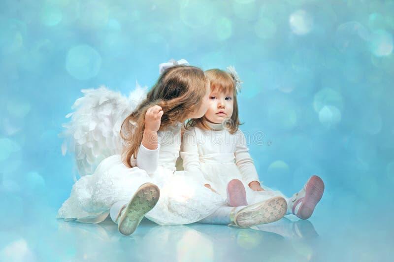 Dos pequeñas hermanas lindas con las alas de un ángel imagen de archivo libre de regalías