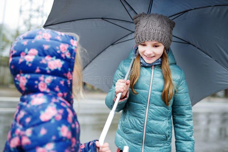 Dos pequeñas hermanas lindas que caminan debajo del paraguas fotografía de archivo