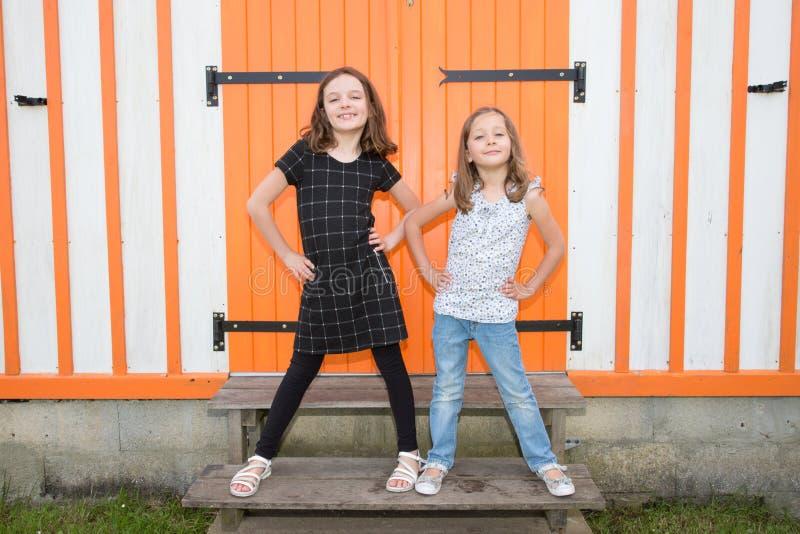 Dos pequeñas hermanas lindas que tienen frente de la diversión de la choza de madera anaranjada junto en ocio al aire libre del v foto de archivo