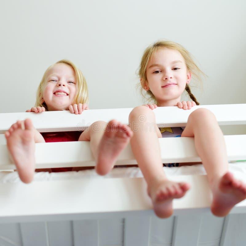 Dos pequeñas hermanas que engañan alrededor, jugando y divirtiéndose en litera gemela imágenes de archivo libres de regalías