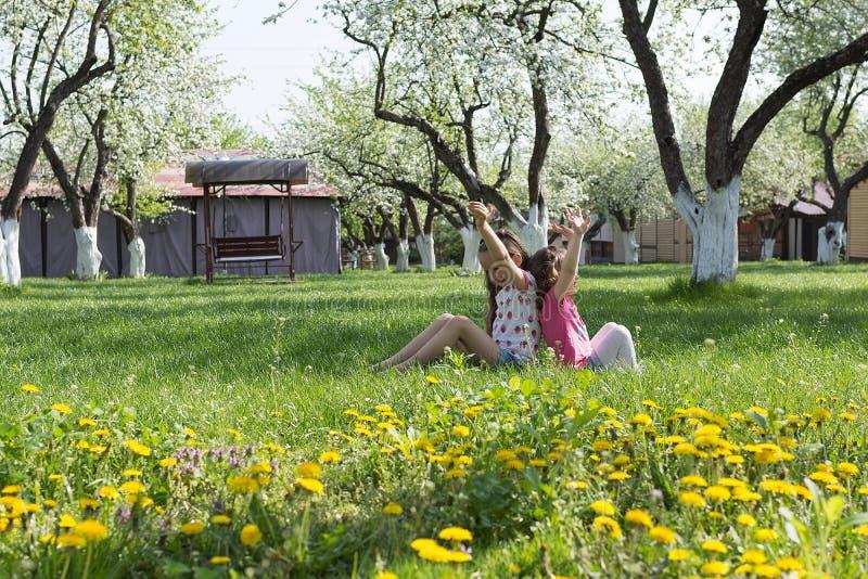 Dos pequeñas hermanas que juegan en el jardín imagenes de archivo