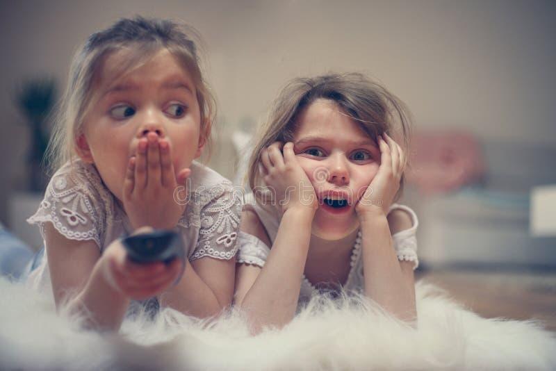 Dos pequeñas hermanas que miran algo el chocar en la TV Ciérreme para arriba imágenes de archivo libres de regalías