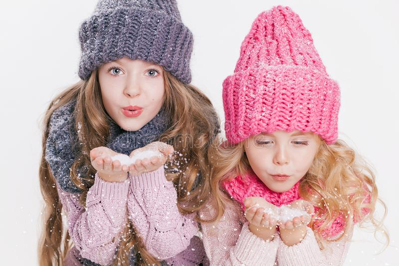 Dos pequeñas hermanas que soplan en los copos de nieve en invierno visten Sombreros y bufandas Color de rosa y gris Familia Invie fotos de archivo