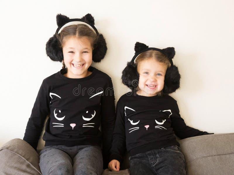 Dos pequeñas hermanas sonrientes se vistieron en los trajes de gatos negros fotos de archivo libres de regalías