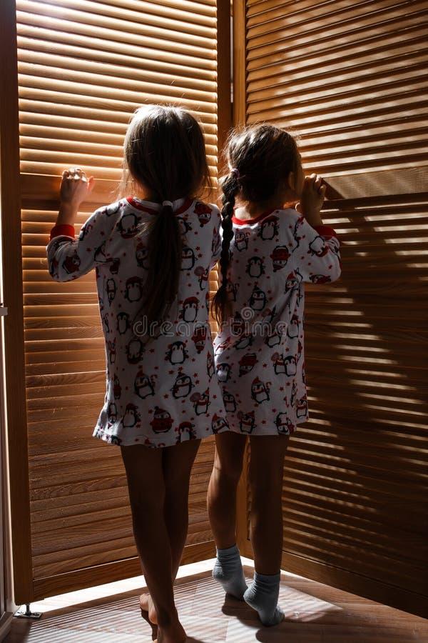 Dos pequeñas hermanas vestidas en los pijamas están ocultando en el armario con las puertas de madera imágenes de archivo libres de regalías