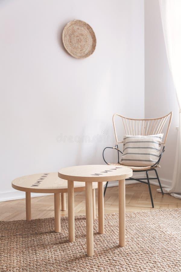 Dos pequeñas mesas de centro y silla de mimbre con la almohada en ella en sala de estar beige natural imagen de archivo libre de regalías