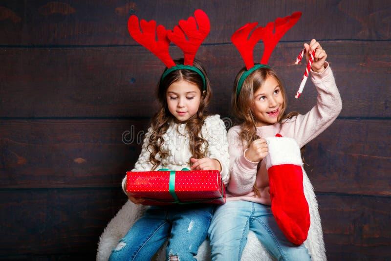 Dos pequeñas muchachas sonrientes felices con las cajas de regalo de la Navidad en fondo de madera Feliz Navidad y Feliz Año Nuev imagen de archivo libre de regalías