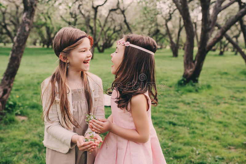 Dos pequeñas novias felices que escogen las flores en jardín de la primavera Hermanas que pasan el tiempo junto al aire libre fotografía de archivo libre de regalías