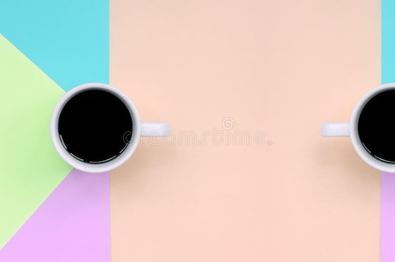 Dos pequeñas tazas del café con leche en el fondo de la textura del papel rosado de la moda, azul, coralino y de la cal en colore fotografía de archivo libre de regalías