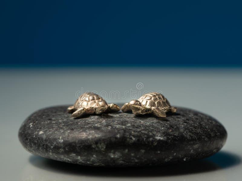 Dos pequeñas tortugas de mar hechas del oro que se sienta en una piedra negra fotos de archivo libres de regalías