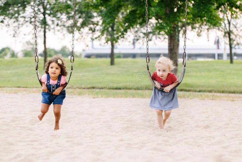 Dos pequeños amigos de muchachas sonrientes felices de los niños que balancean en oscilaciones en el patio afuera foto de archivo libre de regalías
