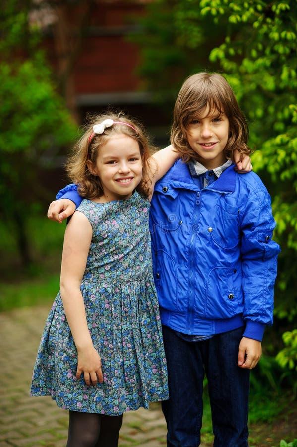 Dos pequeños amigos, el muchacho y la muchacha, soporte que abraza imagenes de archivo