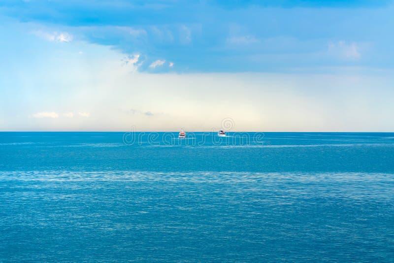 Dos pequeños barcos entran lejos el mar abierto, cielo azul fotografía de archivo libre de regalías
