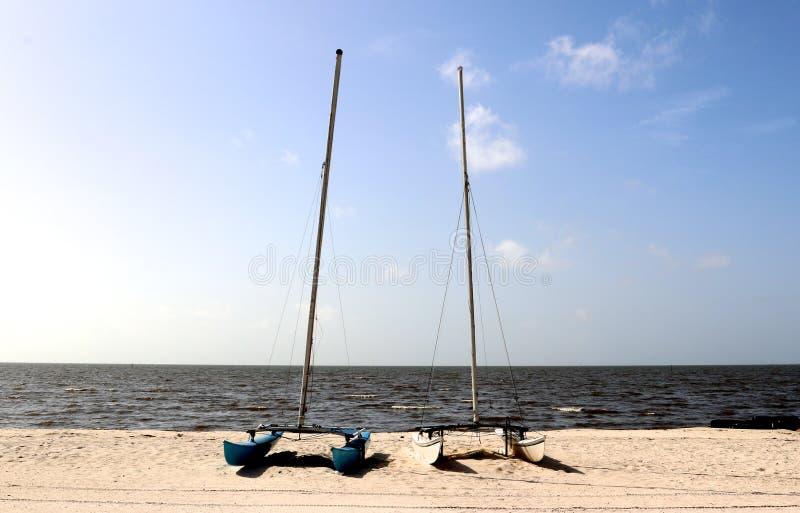 Dos pequeños catamaranes del multihull amarraron en una playa aislada en Biloxi, Mississippi foto de archivo libre de regalías