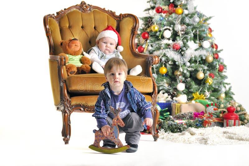 Dos pequeños childs con los juguetes cerca de un árbol de navidad fotos de archivo