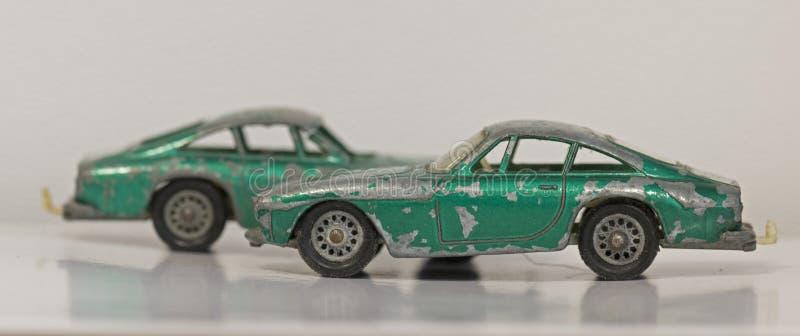 Dos pequeños coches verdes estropeados viejos del juguete del metal fotos de archivo libres de regalías