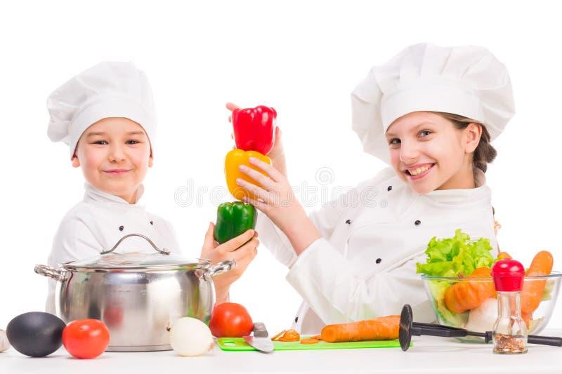 Dos pequeños cocineros que juegan las verduras para la sopa fotografía de archivo