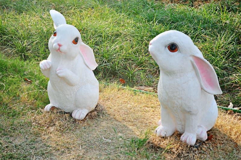 Dos pequeños conejos blancos lindos que se arrodillan en el césped imagen de archivo