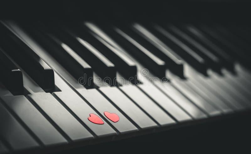 Dos pequeños corazones rojos en el teclado del cierre clásico del piano para arriba Concepto de amor y de música romántica foto de archivo libre de regalías